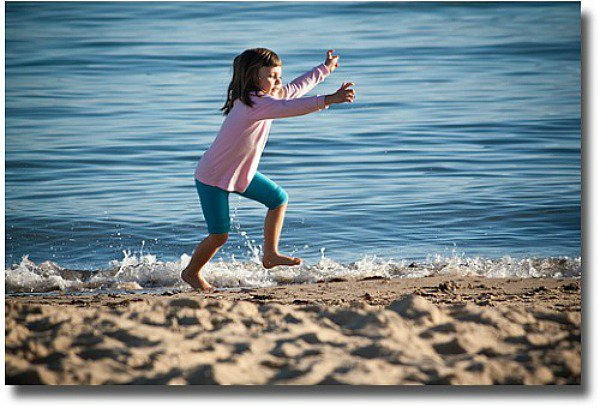 Little girl frolicking in the shallows compliments of http://www.flickr.com/photos/jasvipul/7252618238/